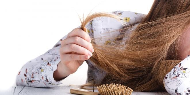 a young woman struggling with tangled hair and split ends